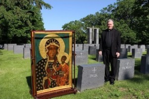 Father West prays with the Black Madonna at the grave of Fr. Paul Marx, founder of HLI.