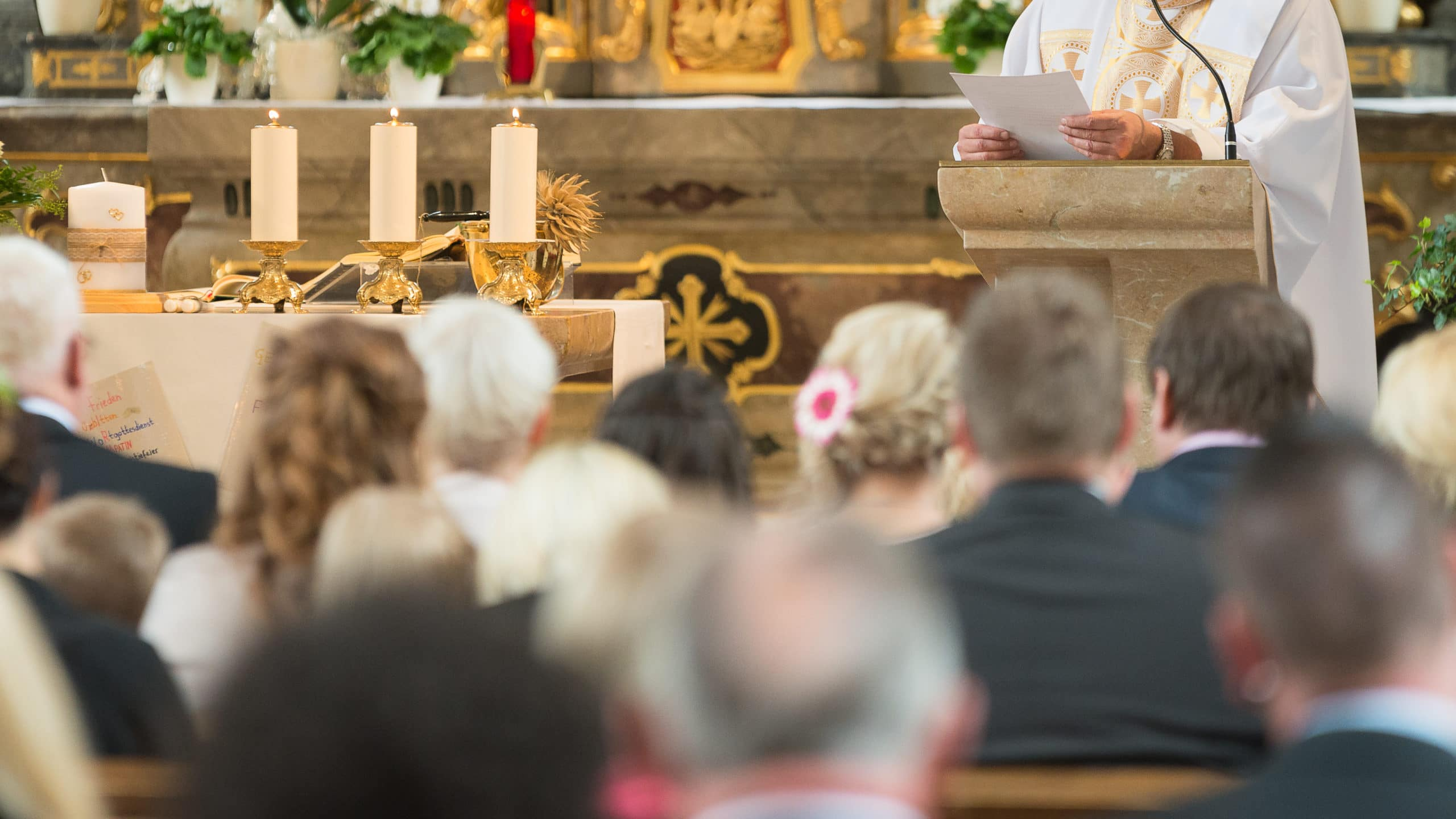 priest giving homily sermon, people listening, in church, catholic Mass