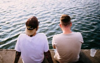 two men sitting at river picture from the back