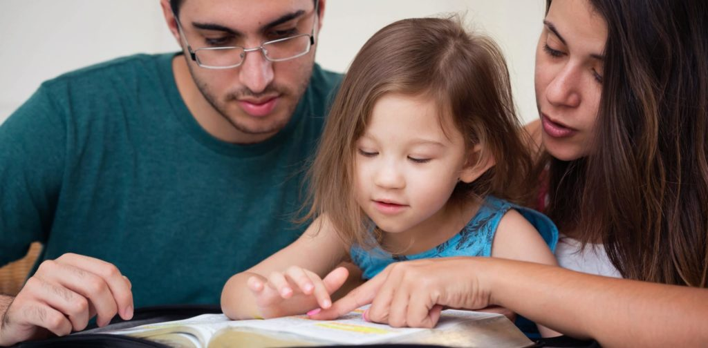parents reading a book with their little daughter