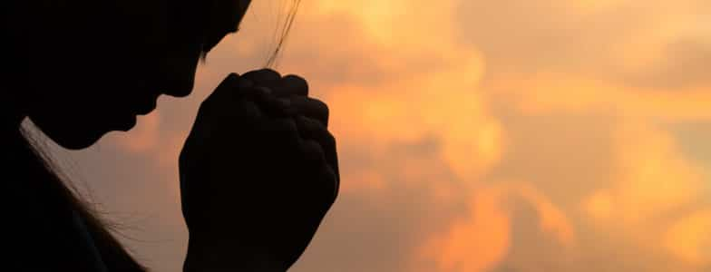 silhouette of a woman praying to God